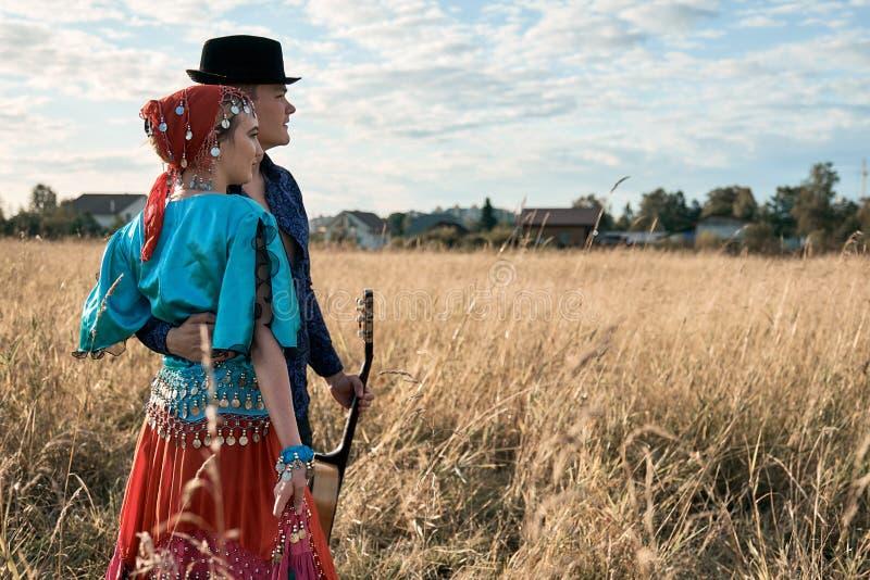 Paare in der Liebe kleideten in der traditionellen Zigeuner-Kleidungsaufstellung an, die auf dem Herbstfeld im Freien ist stockbilder