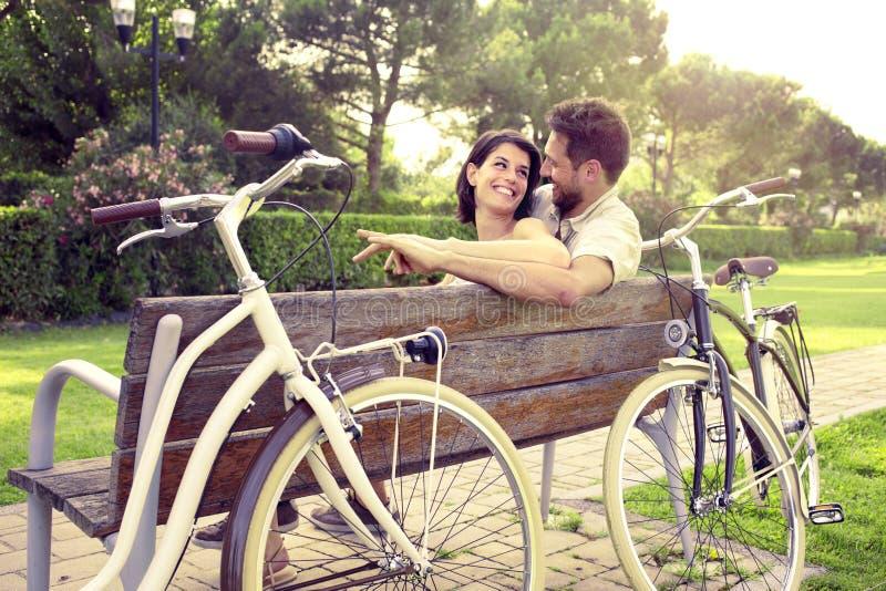 Paare in der Liebe sitted togheter auf einer Bank mit Fahrrädern dazu stockfotos