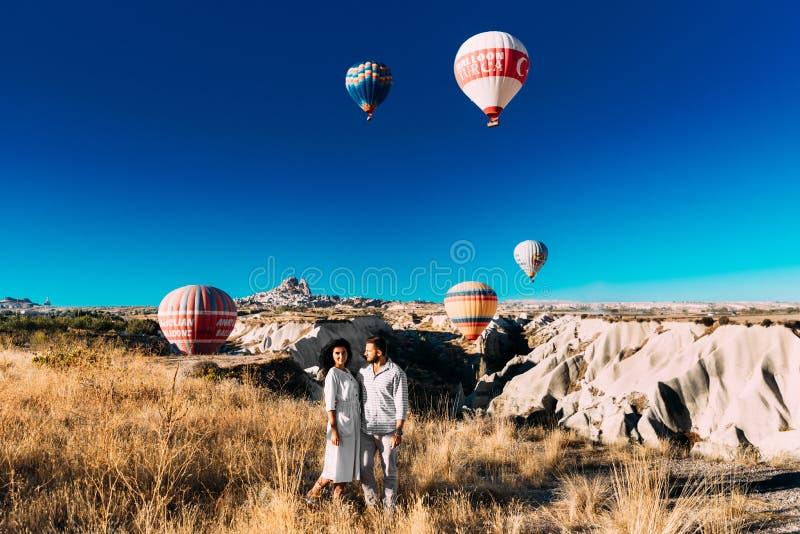 Paare in der Liebe unter Ballonen Glückliches Paar in Cappadocia Flitterwochen in den Bergen Mann- und Frauenreisen Fliegen auf B lizenzfreies stockbild