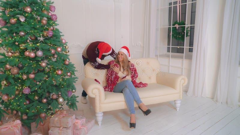 Paare in der Liebe unter Verwendung des Handys im Weihnachten stockbild