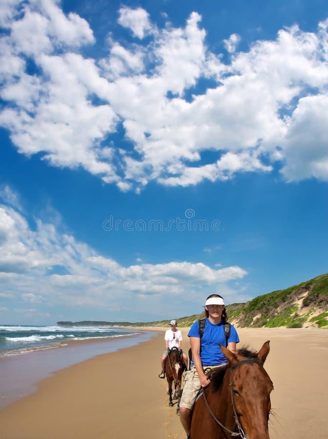 Paare der Mitfahrer auf Strand unter drastischen Himmeln