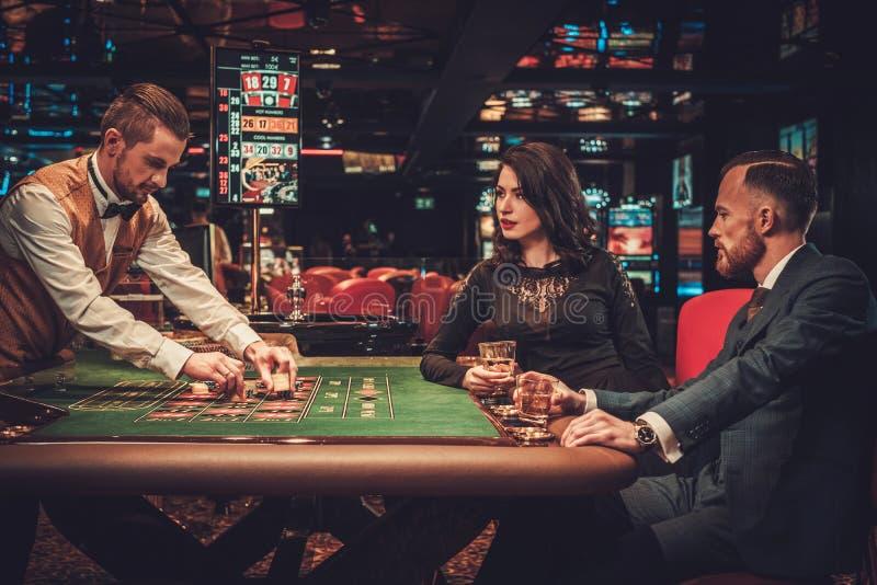 Paare der oberen Klasse, die in einem Kasino spielen stockfoto