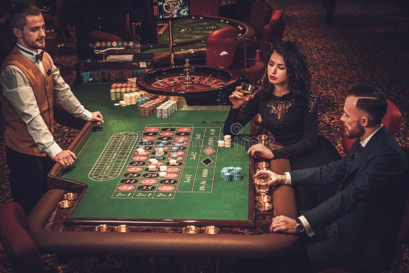 Paare der oberen Klasse, die in einem Kasino spielen stockfotos
