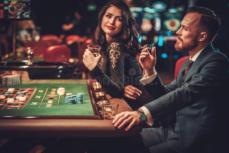 Paare der oberen Klasse, die in einem Kasino spielen stockbild