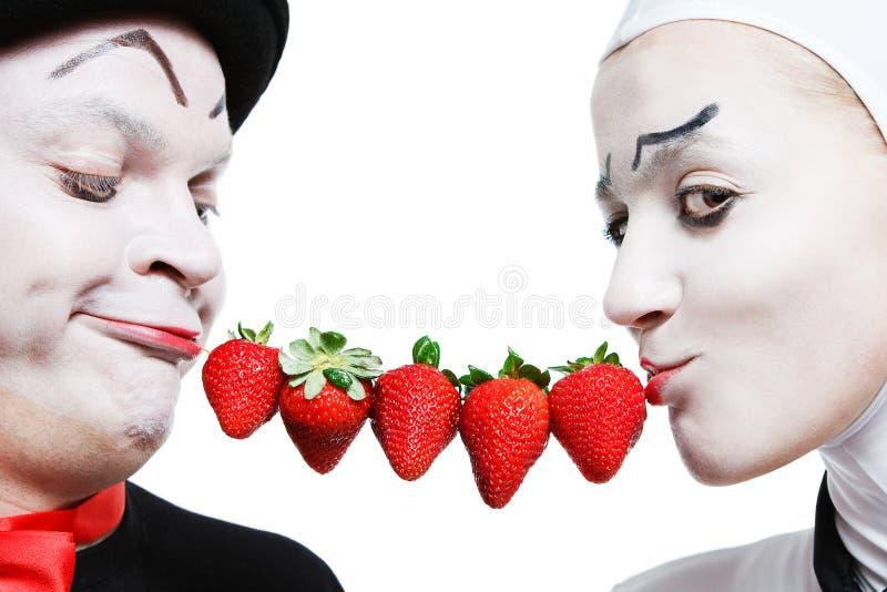 Paare der Pantomimen mit der Erdbeere auf einem weißen Ba stockfoto