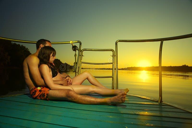 Paare in der Sonnenuntergangumarmung auf Boot lizenzfreies stockbild
