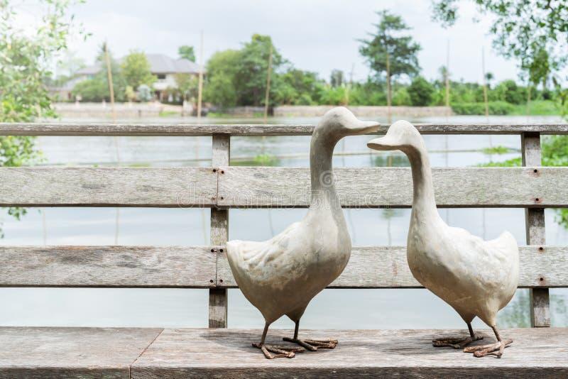 Paare der weißen Gans stehend auf Holzbrücke nahe Fluss, a-Statue von Gans zwei am sonnigen Tag stockbild