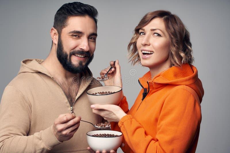 Paare in der zuf?lligen Kleidung, die Corn Flakes mit Milch isst lizenzfreie stockbilder