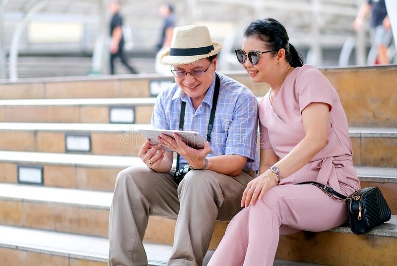 Paare des asiatischen alter Mann- und Frauentouristen betrachten Tablette während des Reisens von Großstadt Dieses Foto auch Konz lizenzfreie stockfotografie