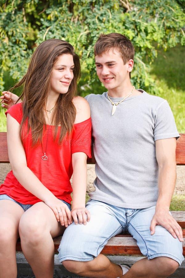 Paare des jungen jugendlich auf einer Bank stockbild
