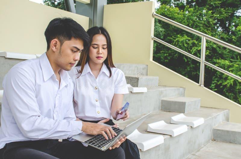 Paare des jungen Mannes des Freunds und der Studentin in Schuluniform Thailand-Art, die an der Hochschulholding-Rabattkreditkarte stockfotos