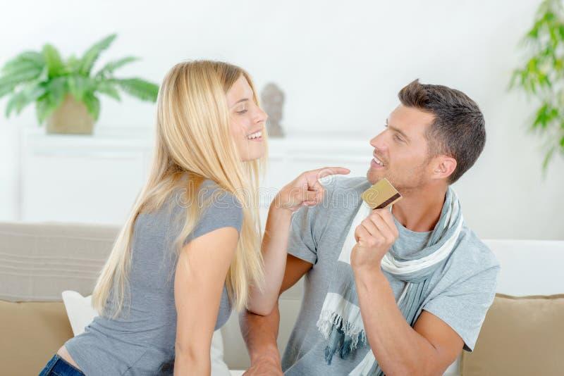 Paare, die über Besitzkreditkarte kämpfen lizenzfreies stockbild