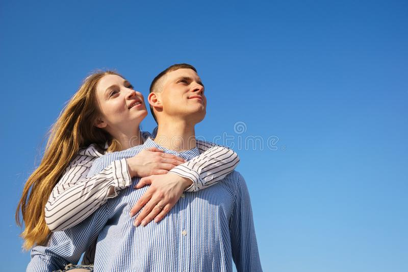 Paare, die über Himmelhintergrund sich umarmen stockbilder