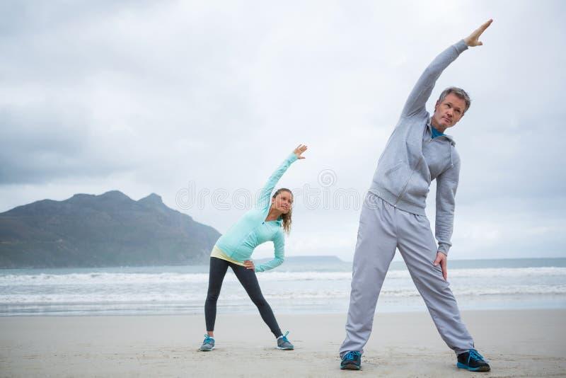 Paare, die Übung auf Strand ausdehnend durchführen lizenzfreies stockbild