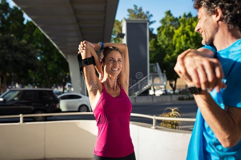 Paare, die Übung in der Straße ausdehnend tun stockbild