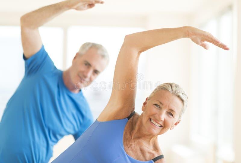 Paare, die Übung zu Hause ausdehnend durchführen lizenzfreie stockbilder