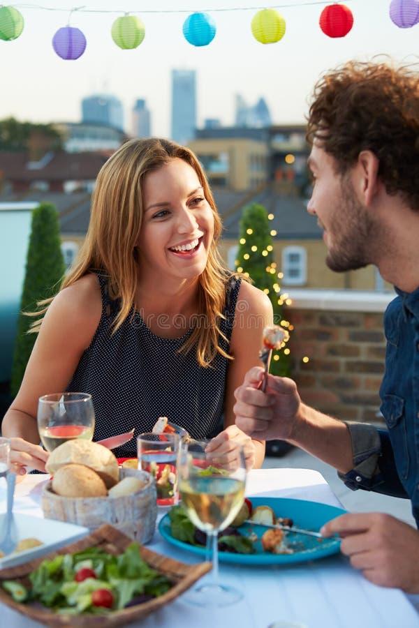Paare, die Abendessen auf Dachspitzen-Terrasse essen lizenzfreie stockbilder