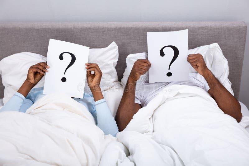 Paare, die auf Bett-Holding-Frage Mark Sign liegen stockfotos