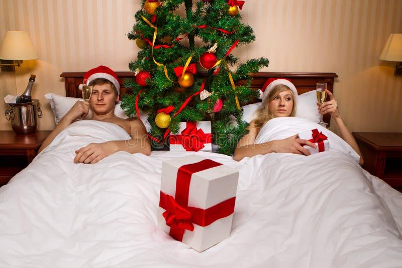 Paare, die auf Bett mit Weihnachtsbaum liegen stockbilder