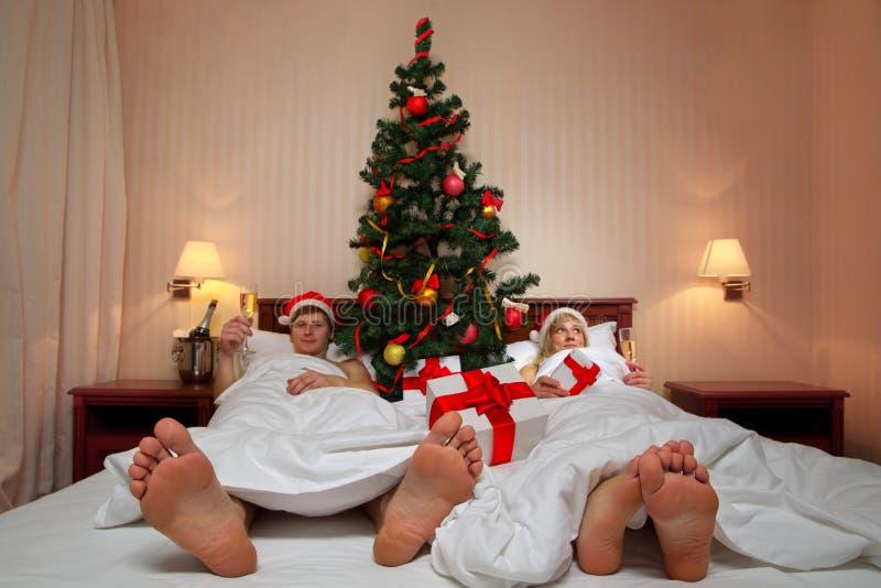 Paare, die auf Bett mit Weihnachtsbaum liegen lizenzfreie stockbilder
