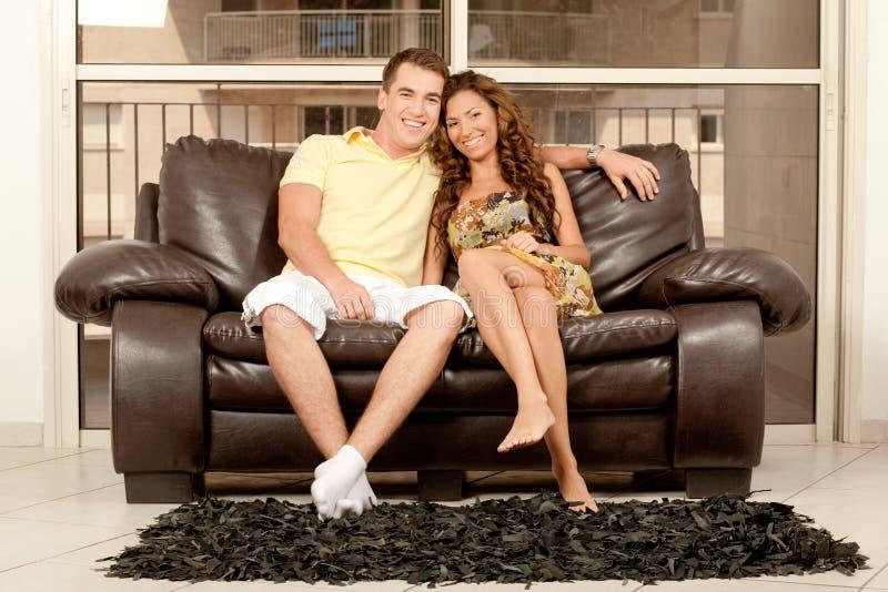 Paare, die auf Couch sich entspannen stockfoto