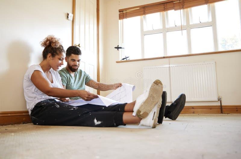 Paare, die auf dem Boden betrachtet Pläne im leeren Raum des neuen Hauses sitzen lizenzfreies stockbild