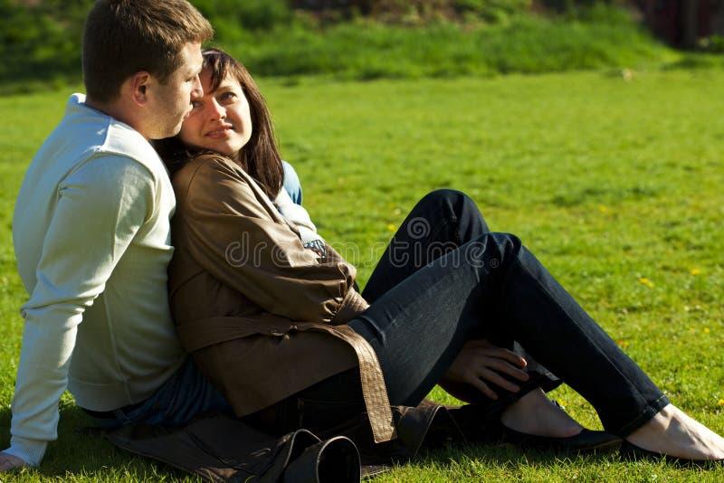 Paare, die auf dem grünen Gras sitzen lizenzfreies stockbild