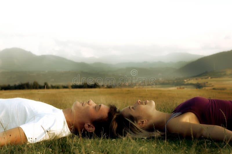 Paare, die auf dem Gras liegen lizenzfreie stockfotos