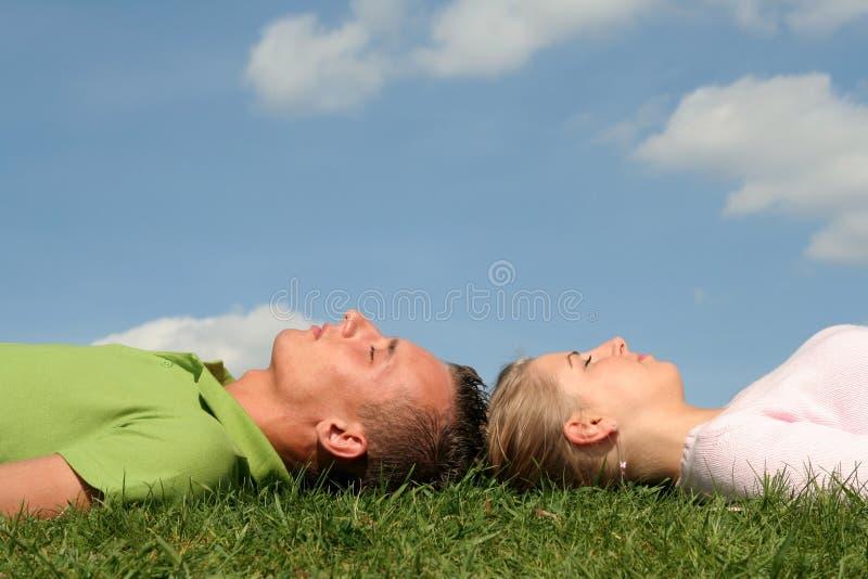 Paare, die auf dem Gras liegen stockfotografie