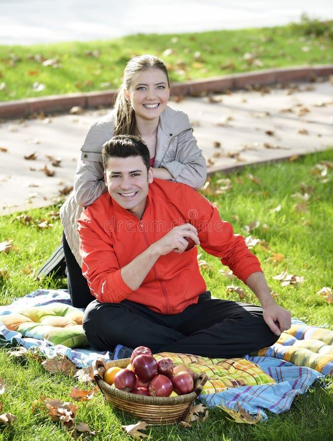Paare, die auf dem Gras sich entspannen und Äpfel essen stockbilder