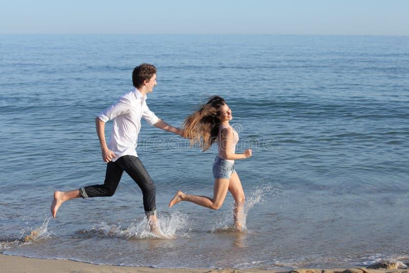 Paare, die auf dem Strand jagen und laufen lizenzfreie stockfotos
