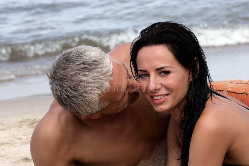 Paare, die auf dem Strand sich entspannen stockfotografie