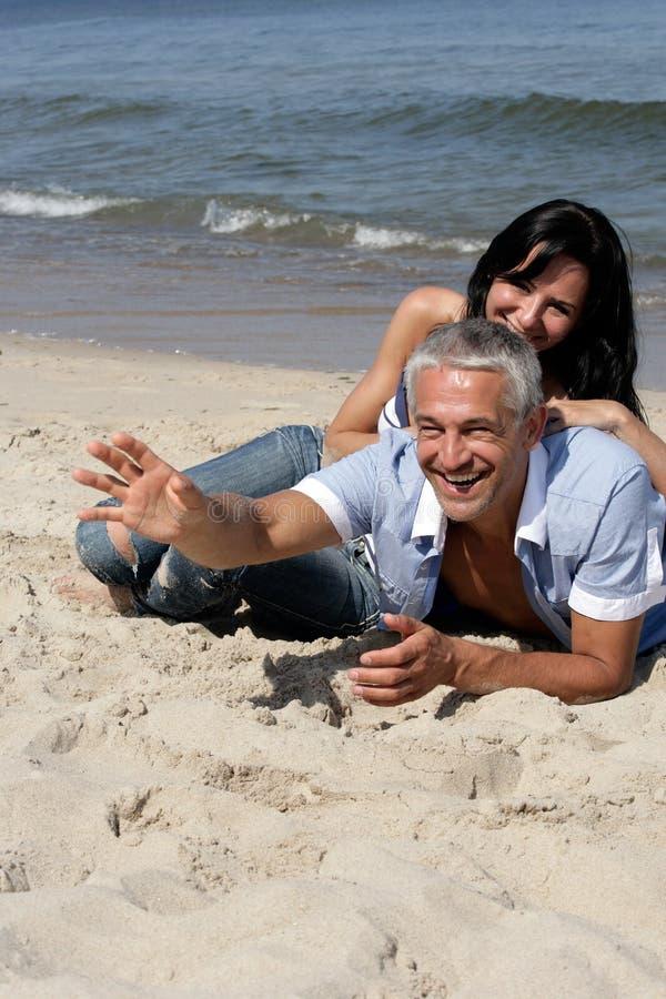 Paare, die auf dem Strand stillstehen stockbild