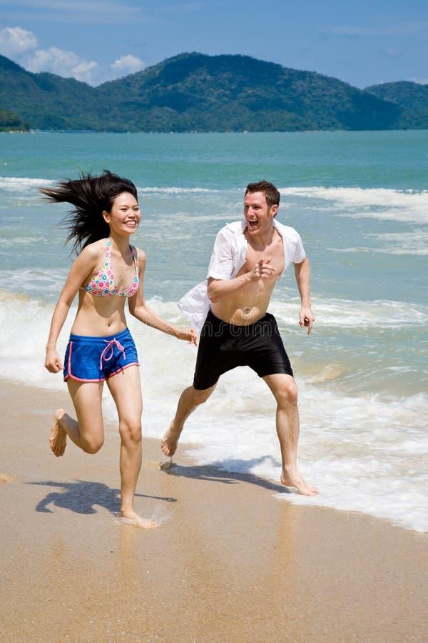 Paare, die auf dem Strandesprit laufen lizenzfreie stockfotografie