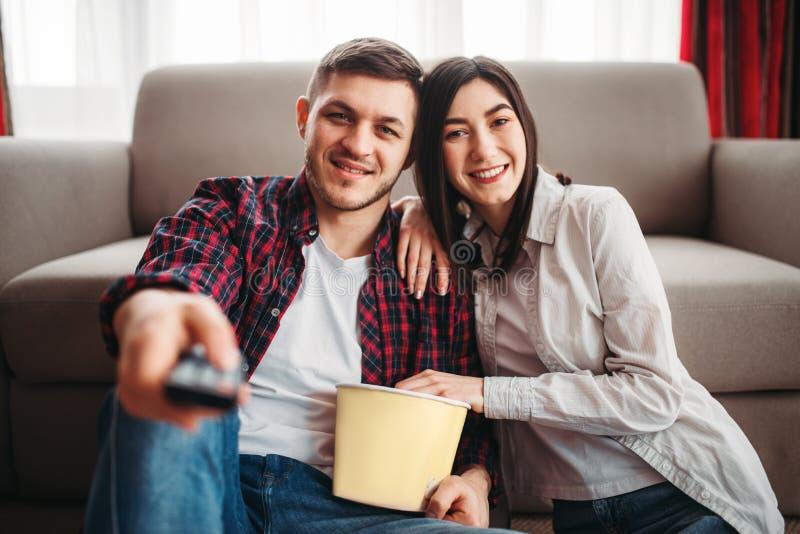 Paare, die auf den Bodenumarmungen und dem Uhrfilm sitzen lizenzfreie stockbilder