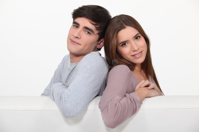 Paare, die auf der Couch sitzen lizenzfreie stockbilder