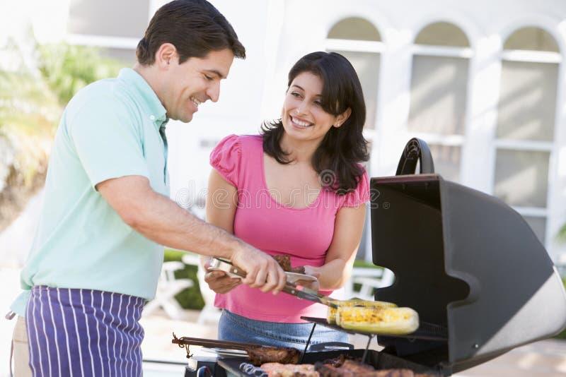 Paare, die auf einem Grill kochen lizenzfreie stockfotografie