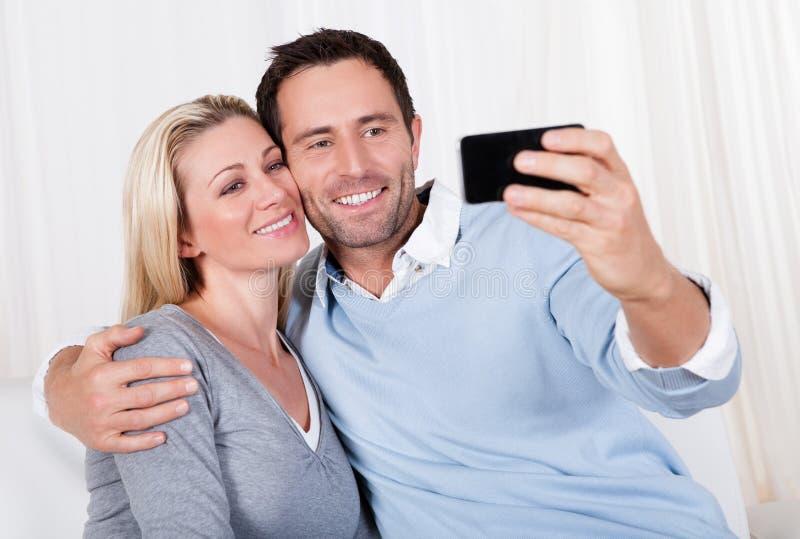 Paare, die auf einem Mobile sich fotografieren lizenzfreies stockfoto