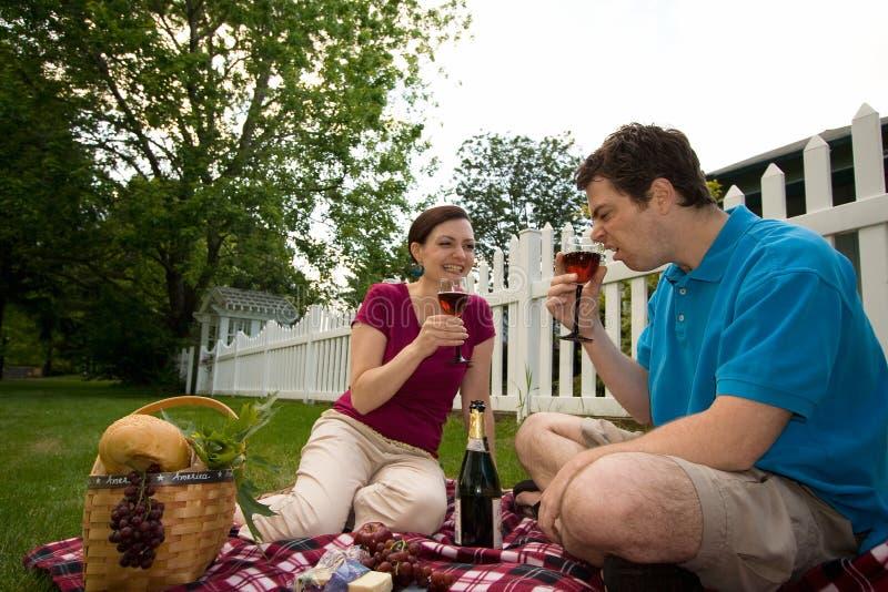 Paare, die auf einem Picknick-Horizontalen scherzen lizenzfreie stockfotografie