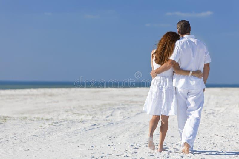 Paare, die auf einen leeren Strand gehen lizenzfreie stockbilder