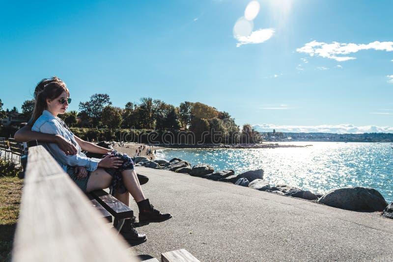 Paare, die auf einer Bank an Kitsilano-Strand in Vancouver, Canad sitzen lizenzfreie stockfotografie