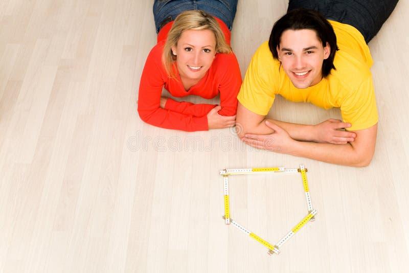 Paare, die auf Fußboden im neuen Haus liegen lizenzfreie stockfotografie