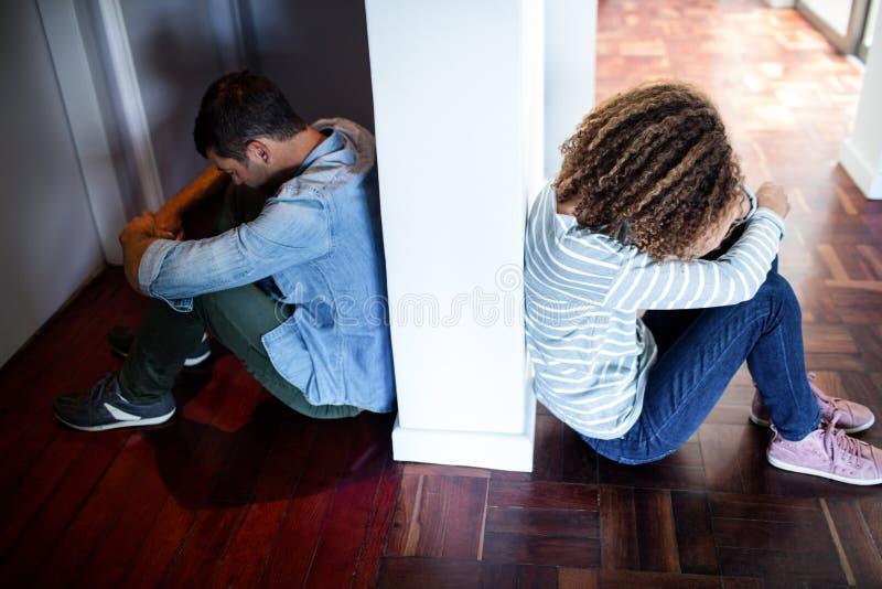 Paare, die auf Gegenseiten der Wand sitzen lizenzfreies stockfoto