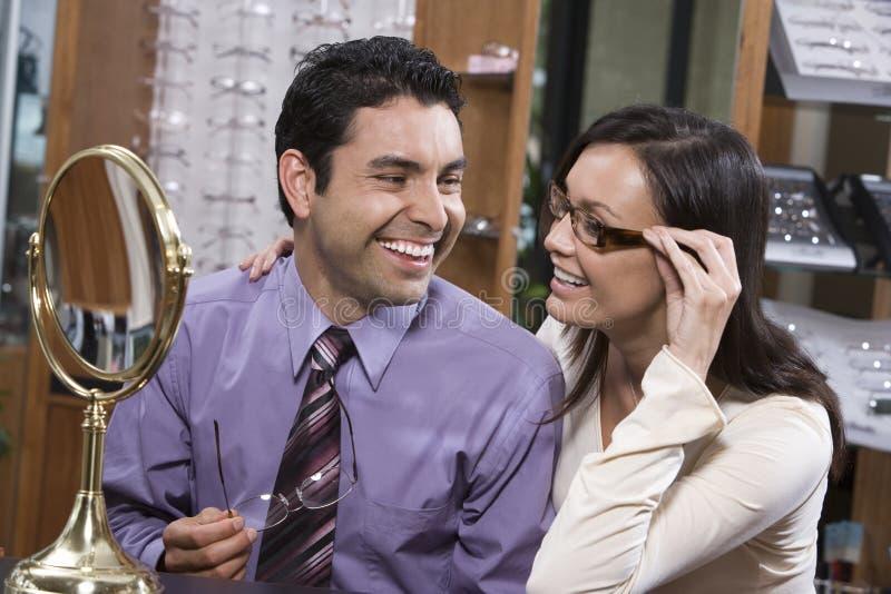 Paare, die auf Gläsern am Geschäft versuchen lizenzfreie stockfotografie