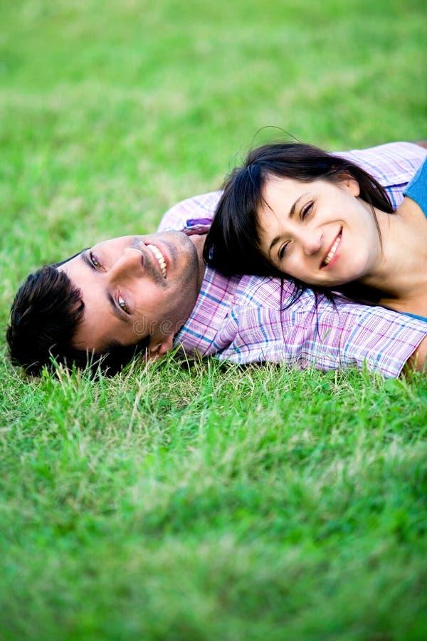 Paare, die auf Gras liegen stockfotografie