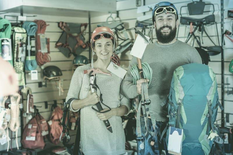 Paare, die auf kletternder Ausrüstung entscheiden stockfotos