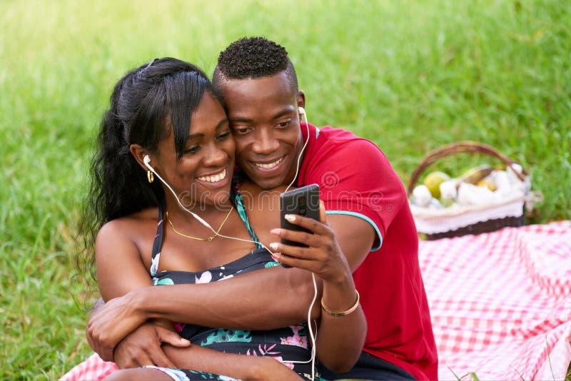 Paare, die auf Musik und aufpassendes Video am Handy hören lizenzfreies stockfoto