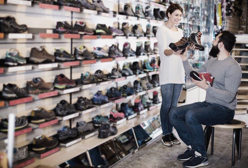 Paare, die auf neuen Turnschuhen entscheiden stockfotos