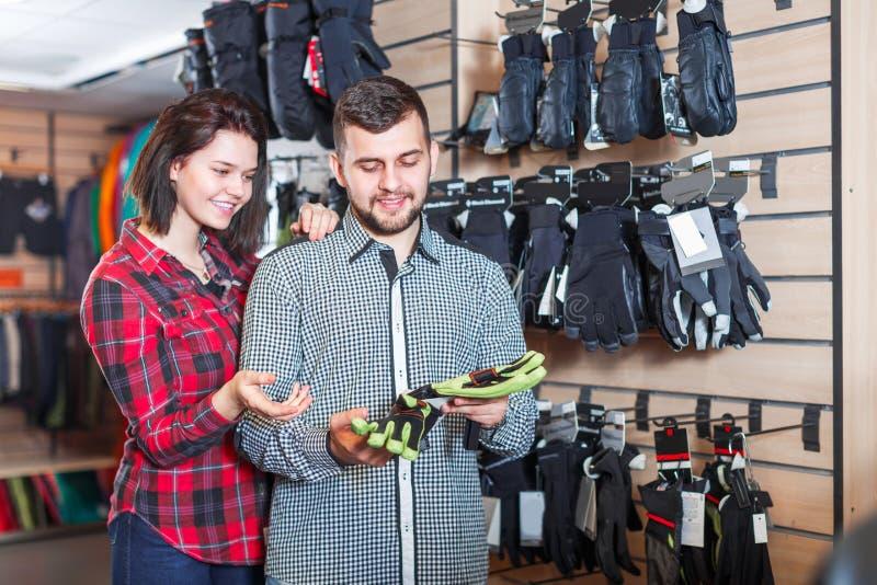 Paare, die auf Schutzhandschuhen entscheiden stockbild