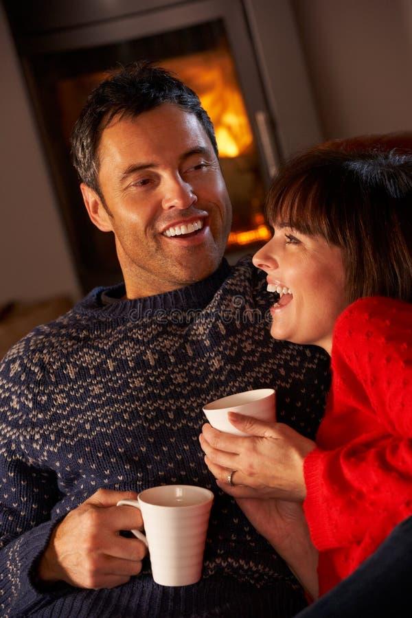 Paare, die auf Sofa durch Cosy Protokoll-Feuer sitzen lizenzfreie stockbilder